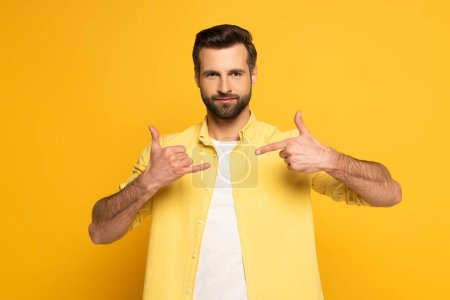 Photo pour Man looking at camera while using deaf and dumb language on yellow background - image libre de droit