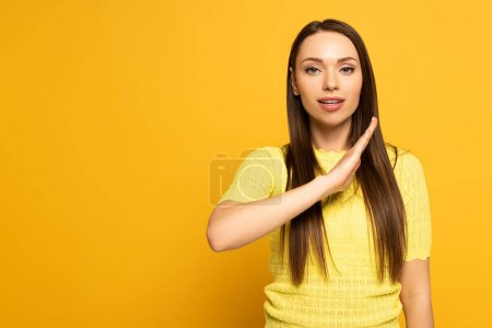 Photo pour Beautiful girl using deaf and dumb language on yellow background - image libre de droit