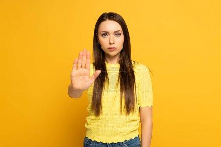 Foto de Muchacha atractiva mostrando gesto de parada mientras mira a la cámara en el fondo amarillo - Imagen libre de derechos