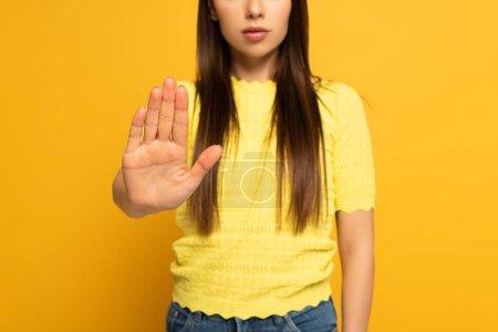 Photo pour Vue recadrée de la femme ne montrant aucun signe sur fond jaune - image libre de droit