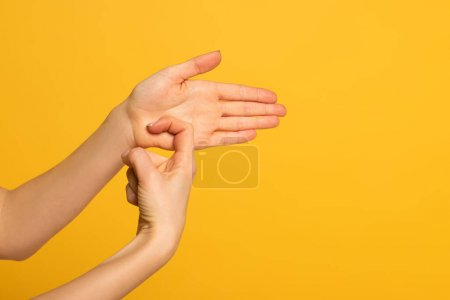 Cropped view of girl using deaf and dumb language isolated on yellow