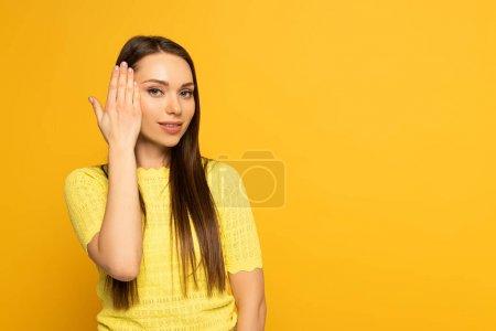 Photo pour Jeune femme regardant la caméra tout en utilisant le langage des signes sur fond jaune - image libre de droit