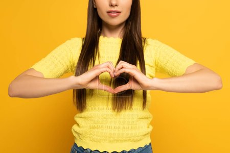 Cropped view of woman showing love sign on yellow background