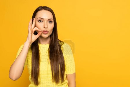 Photo pour Woman with hand near mouth showing sign from deaf and dumb language on yellow background - image libre de droit