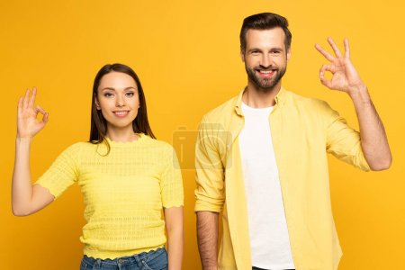 Photo for Smiling young couple showing okay gesture on yellow background - Royalty Free Image