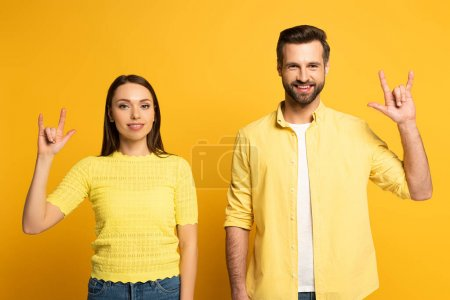Photo for Smiling couple showing rock gesture on yellow background - Royalty Free Image