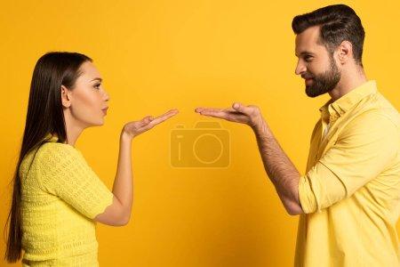 Photo pour Vue latérale d'un jeune couple soufflant de l'air s'embrassant sur fond jaune - image libre de droit