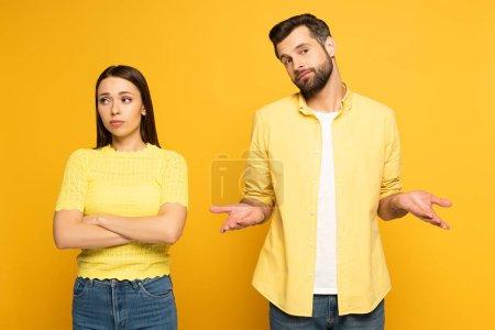 Photo pour Homme confus debout près de petite amie sphérique sur fond jaune - image libre de droit