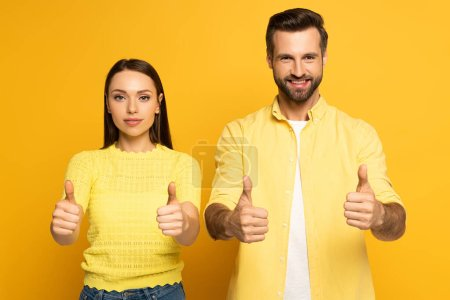 Photo for Young couple showing tums up at camera on yellow background - Royalty Free Image