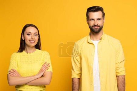 Photo pour Attrayant sourire fille avec les bras croisés regardant caméra près beau petit ami isolé sur jaune - image libre de droit