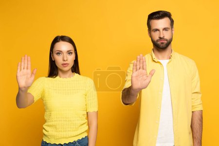 Photo pour Jeune couple montrant geste d'arrêt à la caméra sur fond jaune - image libre de droit