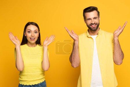 Photo pour Couple joyeux montrant geste haussant les épaules et regardant la caméra sur fond jaune - image libre de droit