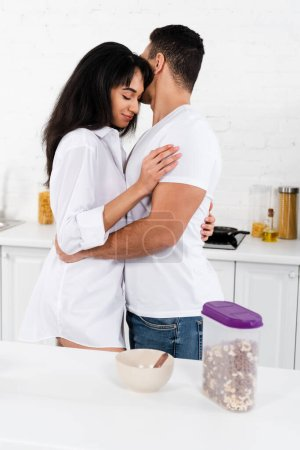 Photo for African american girl with closed eyes smiling and hugging with boyfriend in kitchen - Royalty Free Image