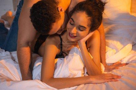 Photo pour Petit ami baisers heureux afro-américaine fille sur le lit dans la chambre - image libre de droit