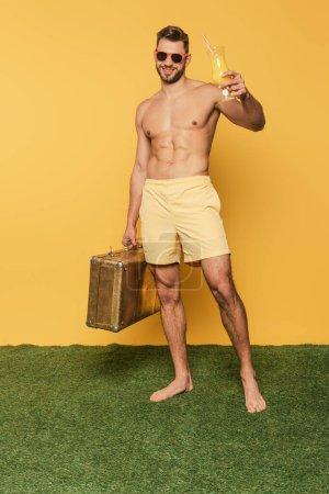 Photo pour Vue pleine longueur de l'homme torse nu heureux tenant verre à cocktail avec du jus d'orange et valise vintage tout en se tenant debout sur l'herbe verte sur fond jaune - image libre de droit