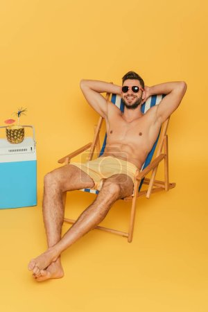 Photo for Smiling shirtless man in sunglasses resting in deck chair near portable fridge and half of pineapple with fresh cocktail on yellow background - Royalty Free Image