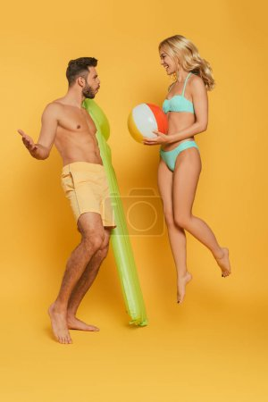 Photo for Cheerful girl jumping with inflatable ball near excited man holding inflatable mattress on yellow background - Royalty Free Image