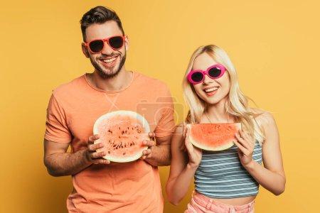 heureux jeune couple dans des lunettes de soleil montrant coupé, pastèque mûre sur fond jaune