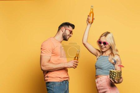 Photo pour Joyeux jeune couple en lunettes de soleil tenant cocktail à l'ananas et bouteilles de bière sur fond jaune - image libre de droit