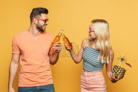 Photo pour Blonde fille tenant un cocktail dans un ananas alors qu'elle claque des bouteilles de bière avec un petit ami souriant sur fond jaune - image libre de droit