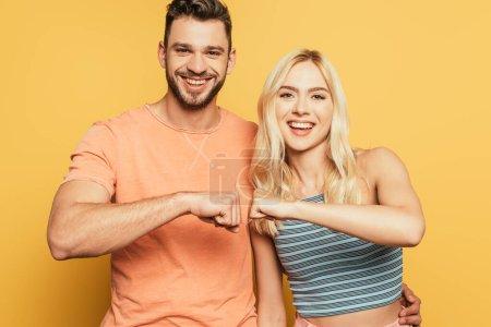 Foto de Feliz joven pareja sonriendo y cámara mientras sostiene puño a puño sobre fondo amarillo - Imagen libre de derechos