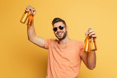 Photo for Cheerful young man in sunglasses holding bottles of beer while smiling at camera on yellow background - Royalty Free Image