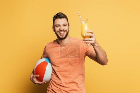 Photo pour Heureux jeune homme tenant ballon gonflable et verre de jus d'orange sur fond jaune - image libre de droit