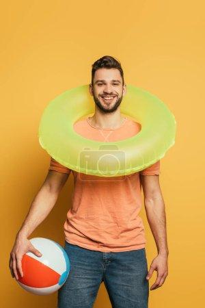 Photo pour Homme heureux avec anneau de natation sur le cou tenant ballon gonflable en regardant la caméra sur fond jaune - image libre de droit