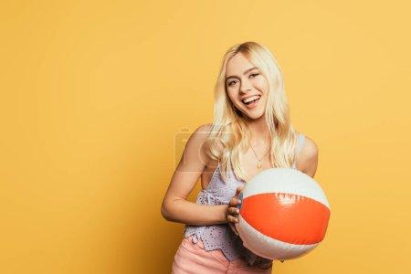 Photo pour Attrayant, fille blonde tenant ballon gonflable tout en souriant à la caméra sur fond jaune - image libre de droit