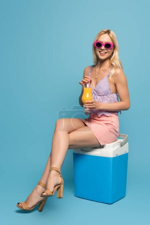 Photo for Attractive, smiling girl sitting on portable fridge with glass of orange juice on blue background - Royalty Free Image