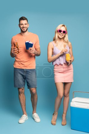 Photo for Happy man with documents and bottle of beer, and smiling girl holding glass of orange juice near portable fridge on blue background - Royalty Free Image