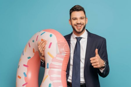 Photo pour Homme d'affaires heureux montrant pouce vers le haut tout en tenant l'anneau gonflable sur fond bleu - image libre de droit