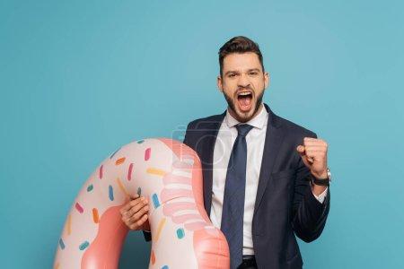 Photo pour Homme d'affaires excité montrant oui geste et crier tout en tenant anneau gonflable sur fond bleu - image libre de droit