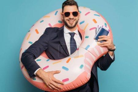 Photo pour Joyeux homme d'affaires en anneau de natation tenant passeport et billets d'appât sur fond bleu - image libre de droit
