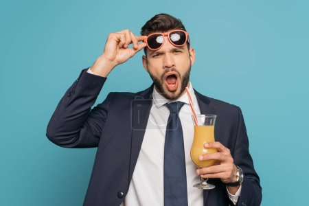 shocked businessman with open mouth touching sunglasses while holding orange juice on blue background