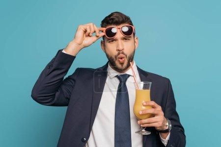 sorprendido hombre de negocios tocando gafas de sol mientras sostiene vaso de cóctel con jugo de naranja aislado en azul