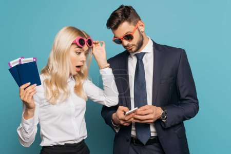 shocked businesswoman holding documents and touching sunglasses while looking at smartphone in hands of businessman on blue background