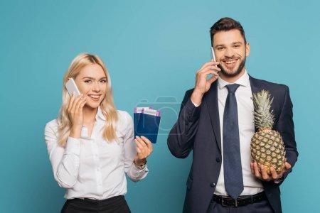 Photo pour Joyeux gens d'affaires parlant sur les smartphones tout en tenant des passeports, des billets d'avion et de l'ananas frais sur fond bleu - image libre de droit