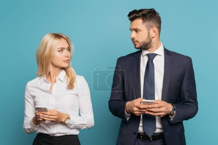 young businesswoman and businessman looking at each other while holding smartphones on blue background