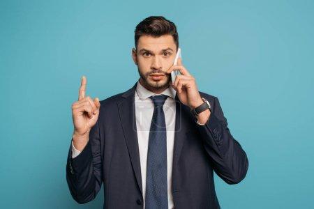 Photo pour Homme d'affaires confiant parlant sur smartphone, montrant geste d'idée et regardant la caméra sur fond bleu - image libre de droit