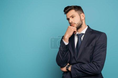 Photo pour Homme d'affaires réfléchi tenant la main près du visage sur fond bleu - image libre de droit