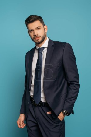 Photo for Serious, handsome businessman looking at camera while holding hand in pocket on blue background - Royalty Free Image