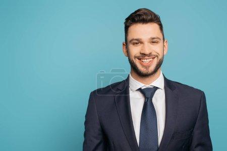 alegre, guapo hombre de negocios sonriendo a la cámara aislado en azul