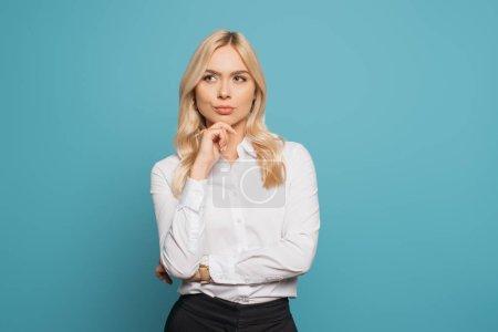 Photo pour Une femme d'affaires pensive tenant la main près du menton tout en regardant loin sur fond bleu - image libre de droit