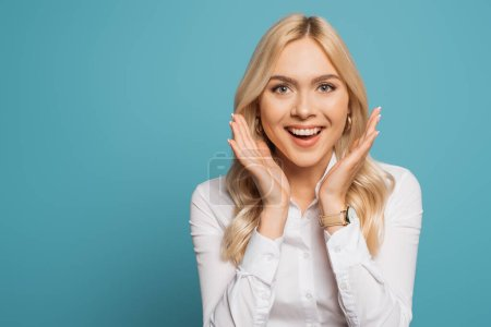 excited businesswoman holding hands near face while looking at camera on blue background