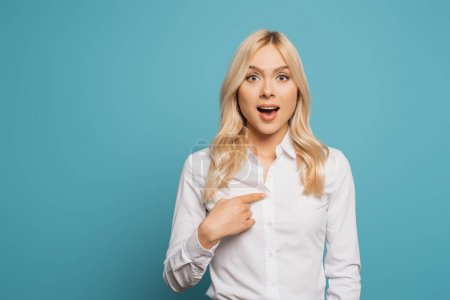Photo for Surprised businesswoman pointing with finger at herself while looking at camera on blue background - Royalty Free Image