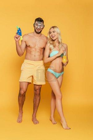 Photo pour Bel homme torse nu masque de plongée tenant pistolet à eau près fille blonde avec un verre de jus d'orange sur fond jaune - image libre de droit