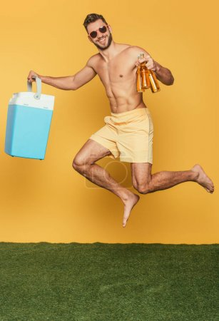 Photo for Happy shirtless man holding portable fridge and bottles of beer while levitating on yellow background - Royalty Free Image