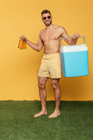 Photo for Cheerful shirtless man holding portable fridge and bottles of beer on yellow background - Royalty Free Image