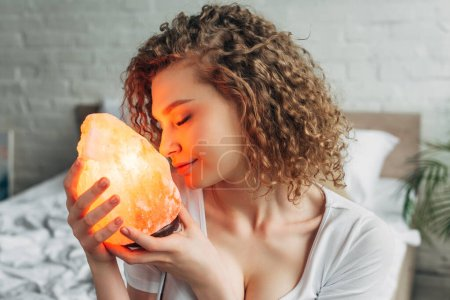 Photo for Attractive dreamy girl with closed eyes holding Himalayan salt lamp in bedroom - Royalty Free Image